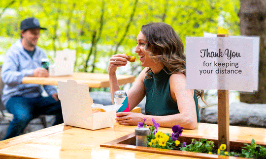 photo of woman eating outside while social distancing